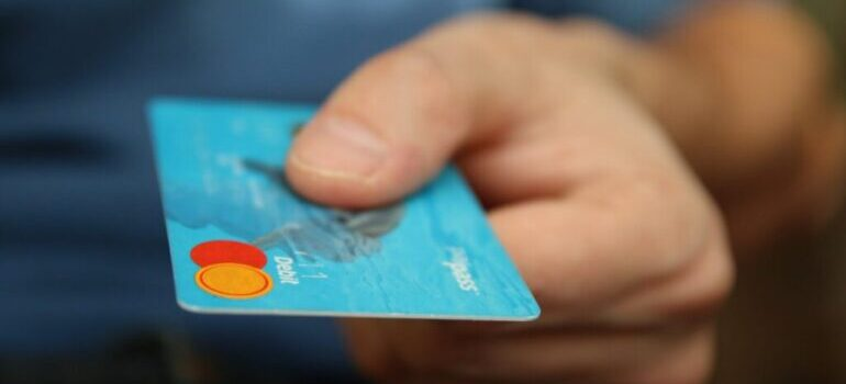 A person holding a blue credit card.