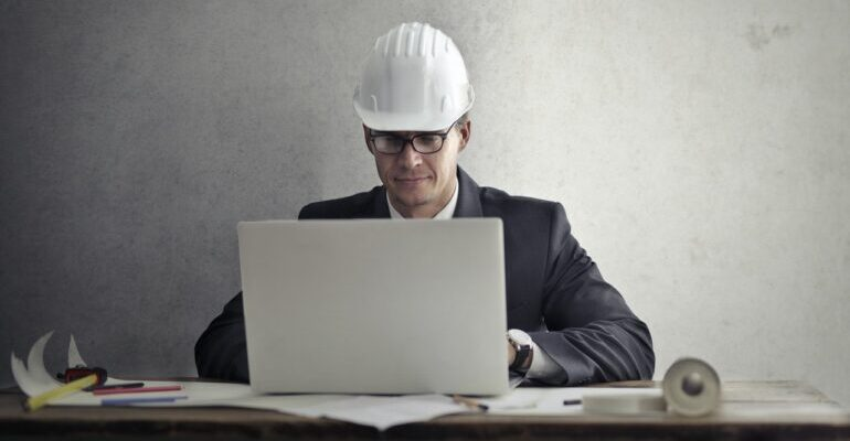 Man with a construction helmet, with a laptop.