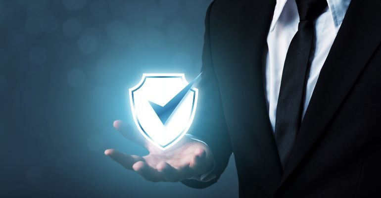 Businessman holding a shield icon with a checkmark.