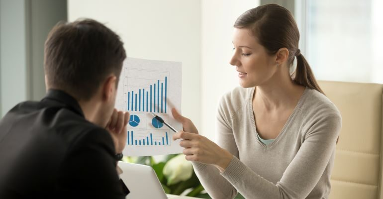 Woman showing growth charts to another person.