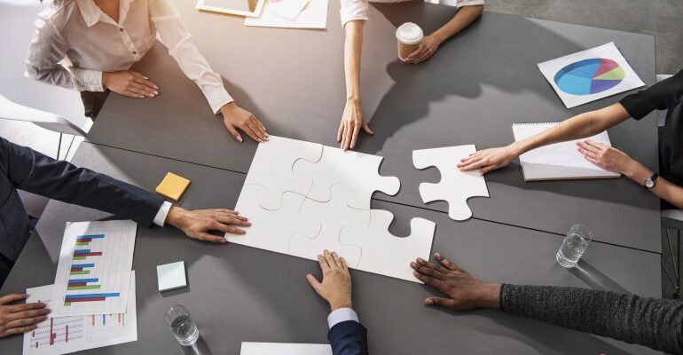 People in a company putting pieces of puzzle together