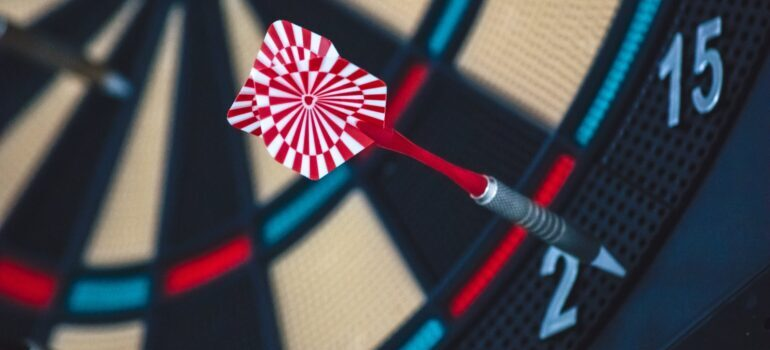 A red and white dart hitting a target.