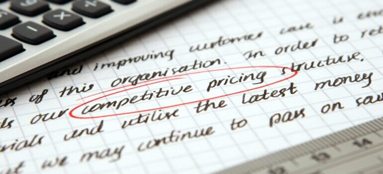 """A close-up of a notebook where """"competitive pricing"""" is circled in red."""