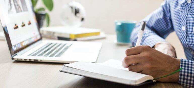A man using a ballpoint pen on a notebook.