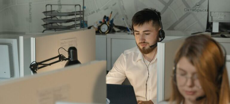 A man in a white shirt working at a call center.