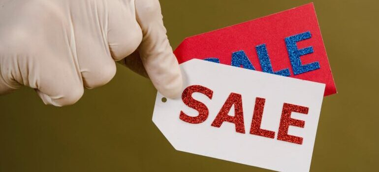 A person holding two sale tags between their fingers.
