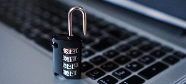 A black open lock on a grey laptop keyboard.