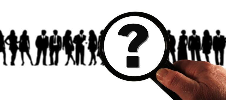 A magnifying glass with a questionmark over black silhouettes of people.