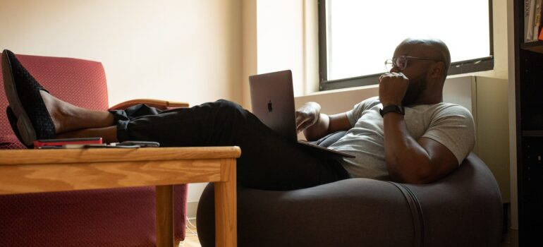 A person lying in a beanbag while working on a laptop.
