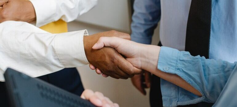 A close-up of two people shaking hands in an office.