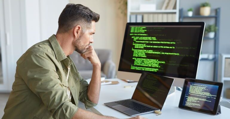 Guy looking at code on screen