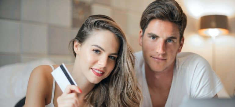 A woman and a man holding a credit card.