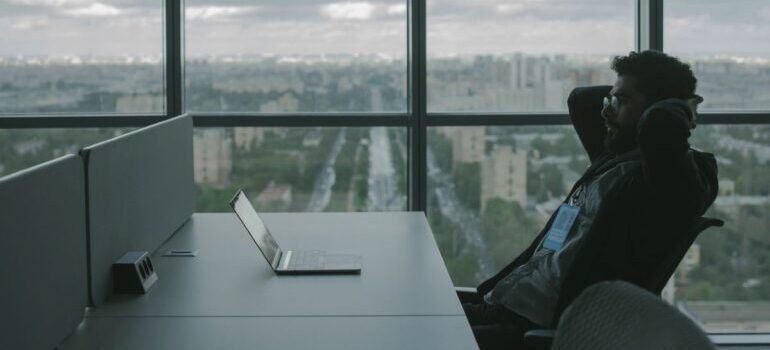 Person with hands on his head, looking at laptop in an office with a view.