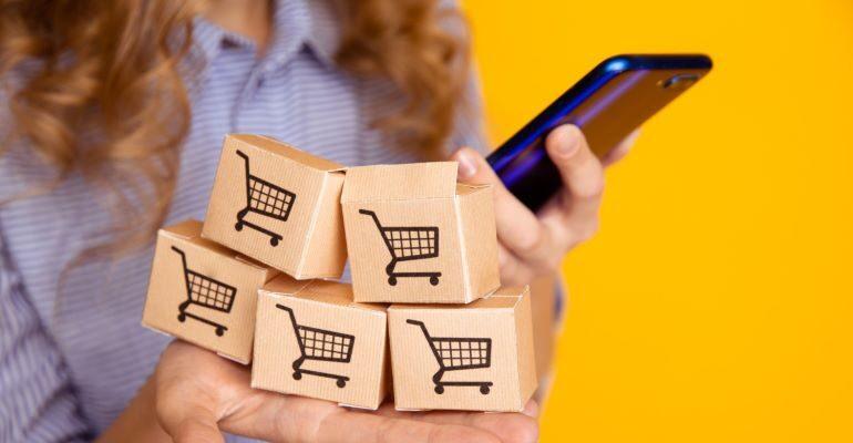Woman with her phone and wooden cubes with shopping carts on them.