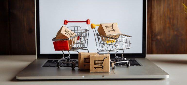 Miniature shopping carts on laptop.