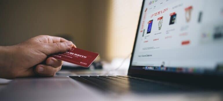 A person holding a credit card and looking at an eCommerce website on a laptop.