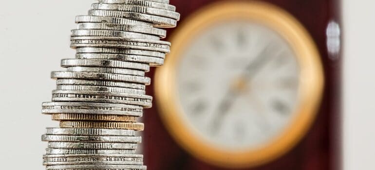 Stacked up coins with a clock in the background.