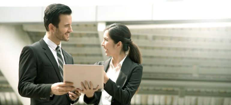 A businessman and businesswoman looking at laptop and smiling.