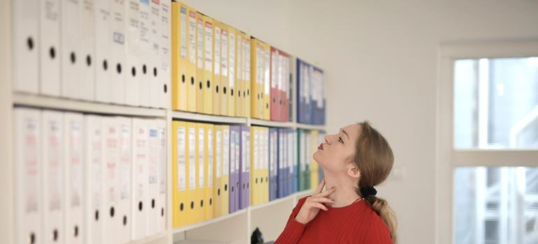Woman looking at document file folders.