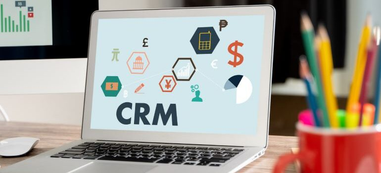 Vector image of different currencies on laptop screen, alongside CRM.