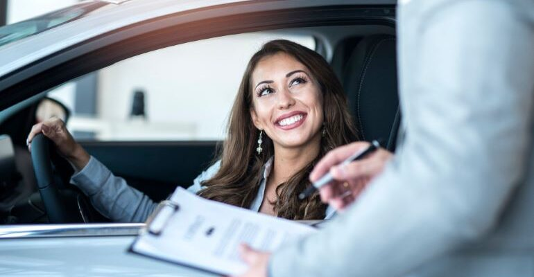 Woman in car being interviews to give her customer feedback.