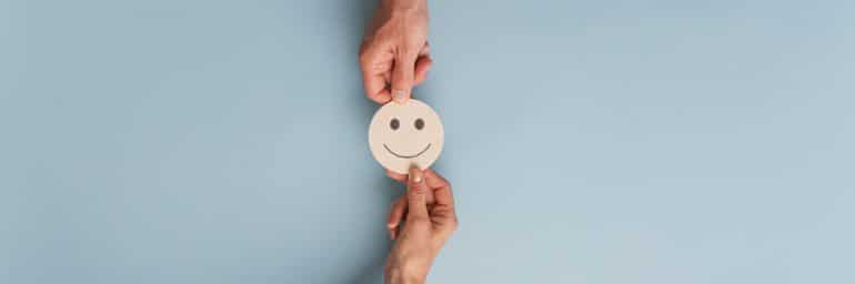 Two hands passing a wooden smiley face token.