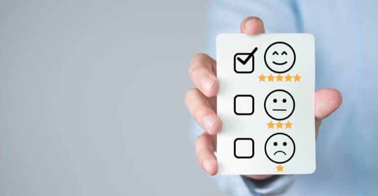 Checkboxes next to a smiley face, indifferent face, and a sad face, and a person placing a checkmark next to the indifferent face.