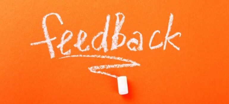 Feedback written with white chalk on orange board.