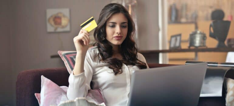 A woman using a credit card while looking at a laptop.