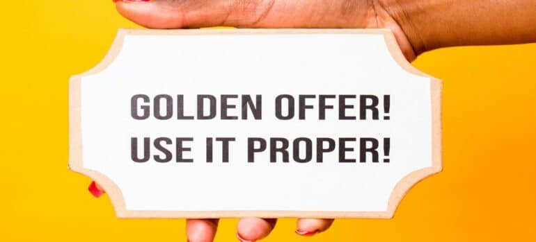 """A hand holding a sign that says """"Golden offer! Use it proper!"""""""