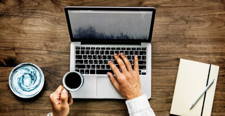 Person looking at laptop, with cup of coffee in hand.