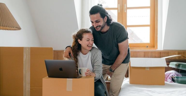 A happy couple, looking for moving services online.