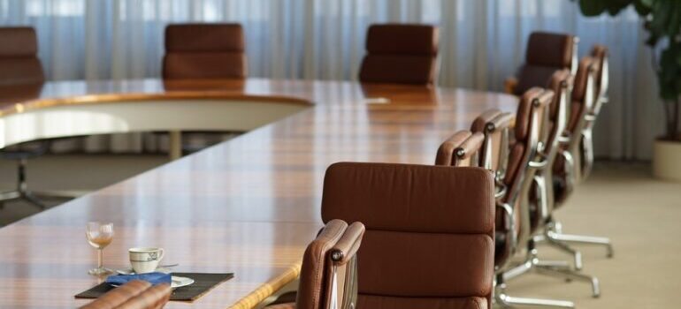 A round conference table with brown leather seats.