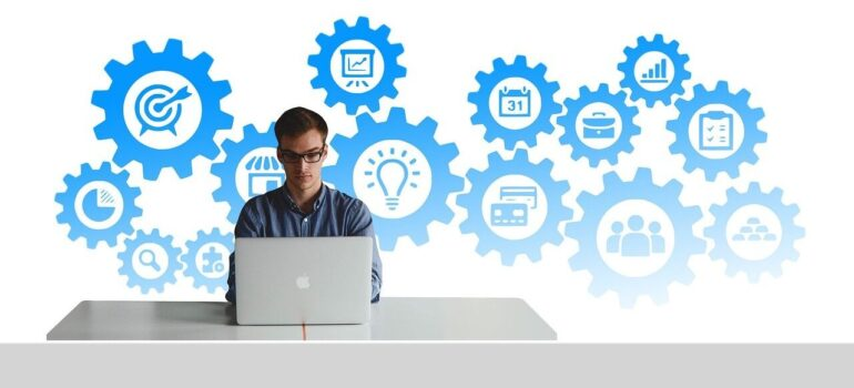 A person working on Guidelines for nurturing moving leads long-term with software cogs behind him.
