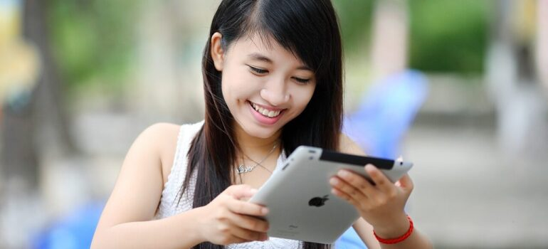 A girl smiling while reading something on a portable PC.