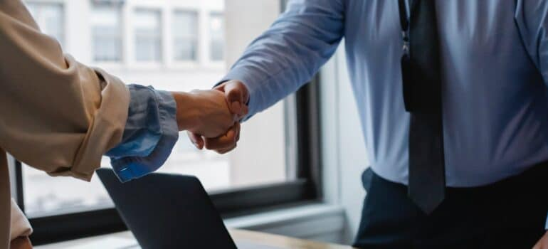 People in professional attire shaking hands.