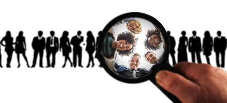 A person using a magnyfing glass on a group of people, representing one way in which CRM helps reduced sales teams stay efficient.