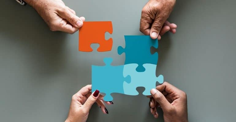 Four people putting large puzzle pieces together.