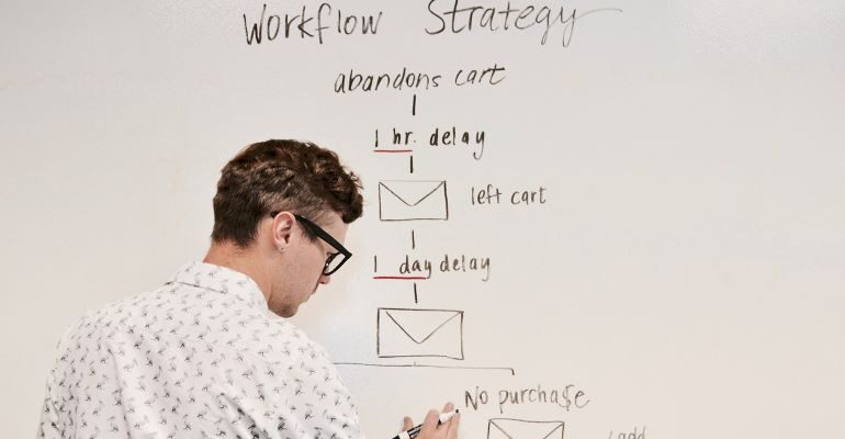 A person drawing a workflow chart on a blackboard.