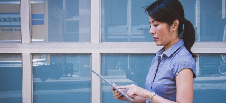 A woman holding a tablet and reading about boosting your marketing analytics skills.
