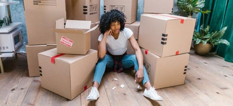 Woman sitting next to cardboard boxes.