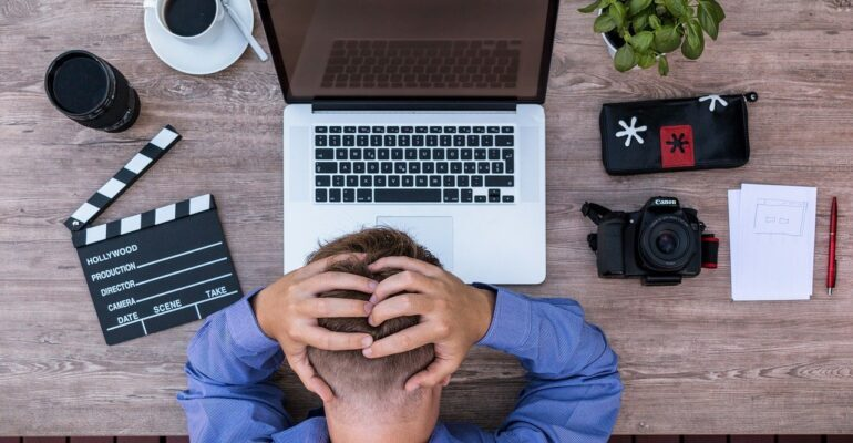 An employee holding his head in a nervous way in front of a laptop.